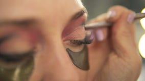 Artiste de maquillage appliquant le fard à paupières à l'oeil modèle du ` s Fermez-vous vers le haut de la vue connexions clips vidéos