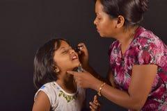 Artiste de maquillage appliquant le fard à paupières à une petite fille, Pune photographie stock libre de droits