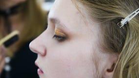 Artiste de maquillage faisant la belle fille de maquillage dans le salon, le concept de beauté et le style clips vidéos