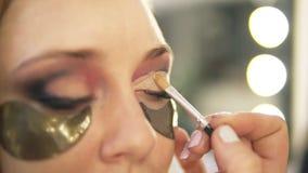 Artiste de maquillage mettant sur les ombres de yeux légères sur l'oeil modèle du ` s Fin vers le haut connexions Vue de côté banque de vidéos