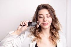 Artiste de maquillage mignon de brune utilisant la brosse de maquillage photo stock