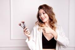 Artiste de maquillage mignon de brune utilisant la brosse de maquillage images stock