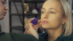 Artiste de maquillage professionnel au plan rapproché de main de brosse de travail - maquillage professionnel des coulisses de co clips vidéos