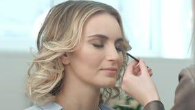 Artiste de maquillage professionnel peignant des cils de modèle dans la chambre blanche Images libres de droits