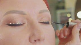 Artiste de maquillage s'appliquant le maquillage à l'oeil modèle du ` s Fermez-vous vers le haut de la vue clips vidéos
