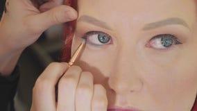 Artiste de maquillage s'appliquant le maquillage à l'oeil modèle du ` s Fermez-vous vers le haut de la vue banque de vidéos