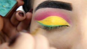 Artiste de maquillage s'appliquant le maquillage de fard à paupières au ` modèle s banque de vidéos