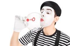 Artiste de pantomime soufflant une bulle par la baguette magique Image libre de droits
