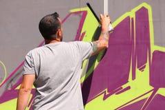 Artiste de rue peignant le graffiti coloré sur le mur - concept d'art moderne avec les murales vivants de peinture urbaine de typ image stock