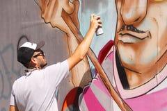 Artiste de rue peignant le graffiti coloré sur le mur - concept d'art moderne avec les murales vivants de peinture urbaine de typ image libre de droits