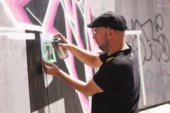 Artiste de rue peignant le graffiti coloré sur le mur - concept d'art moderne avec les murales vivants de peinture urbaine de typ images libres de droits