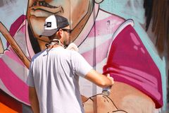 Artiste de rue peignant le graffiti coloré sur le mur - concept d'art moderne avec les murales vivants de peinture urbaine de typ photographie stock libre de droits