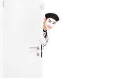 Artiste de sourire de pantomime posant derrière une porte en bois Images stock