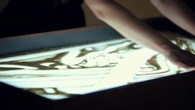 Artiste Draws Two People sur le sable banque de vidéos
