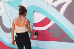 Artiste féminin de rue peignant le graffiti coloré sur le mur - concept d'art moderne avec les murales vivants de peinture urbain images libres de droits