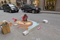 Artiste féminin peignant la naissance de Vénus sur le trottoir près de Calim Image stock