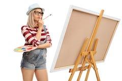 Artiste féminin regardant une peinture images stock