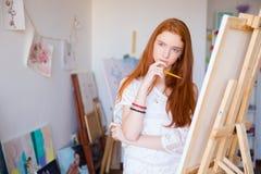 Artiste féminin songeur attirant pensant et dessinant sur la toile images libres de droits