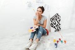 Artiste heureux de jeune dame s'asseyant sur le plancher Images libres de droits