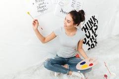 Artiste heureux de jeune dame s'asseyant sur le plancher au-dessus du fond blanc Images stock