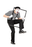 Artiste masculin de pantomime marchant par un cadre en métal photo libre de droits
