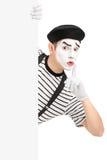 Artiste masculin de pantomime tenant un panneau vide et faisant des gestes l'esprit de silence Photo libre de droits