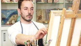 Artiste masculin mûr travaillant à une peinture à son studio d'art Photos stock
