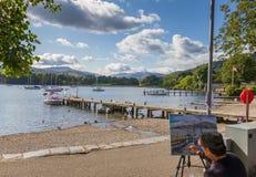Artiste peignant le lac et un pilier dans Ambleside dans le lac Windremere Photographie stock libre de droits