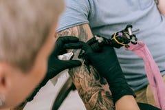 Artiste précis précis faisant l'ombrage pour le tatouage massif images stock