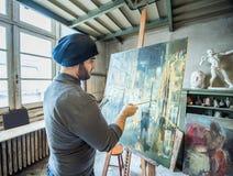 Artiste/professeur peignant une illustration pour un concours dans son studio photos libres de droits