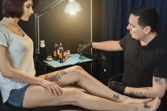 Artiste professionnel de tatouage faisant le tatouage sur la jambe photo libre de droits