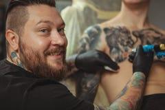 Artiste professionnel de tatouage faisant un nouveau tatouage pour son client images libres de droits