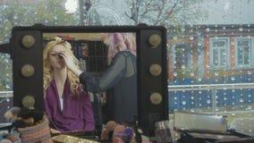 Artiste professionnel faisant à maquillage la jeune jolie femme d'affaires banque de vidéos
