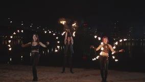 Artistes habiles de fireshow jonglant le feu par la rivière banque de vidéos