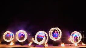 Artistes jonglant avec le poi& brûlant x27 ; s à la représentation de feu images stock