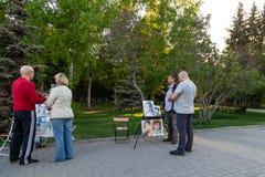 Artisti con le immagini della gente ai cavalletti nell'offerta del parco della città per estrarre un ritratto ai passanti un chia immagini stock libere da diritti