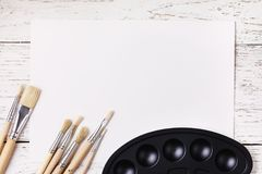 Artistic accessories: Empty palette and brush for drawing. On a wooden table with space for text, top view Stock Photo