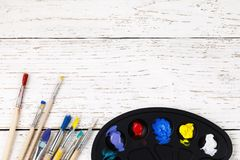 Artistic accessories: a palette with paints and tassels. For drawing on a wooden table with space for text, top view Stock Photos