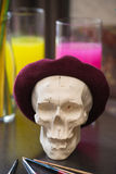 Artistic atmosphere: vase with colored water, skull in beret. creative mood. Royalty Free Stock Photography
