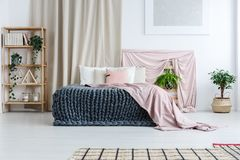Artistic bedroom with pastel cloths. Wooden shelf with plants next to king-size bed with knit blanket and pink coverlet in artistic bedroom with pastel cloths Stock Images
