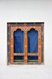 Artistic Bhutanese windows with blue curtain Stock Photos