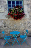 Artistic blue tables and chairs. Artistic blue tables and chairs set with a blue window and flowers.Typically french Royalty Free Stock Photo