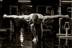 Artistic bodybuilder. Artistic training shot of young muscular man in the gym Royalty Free Stock Photography
