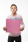 The artistic boy brunette in a pink jumper with a pink sheet of paper for notes. On a white background Royalty Free Stock Images