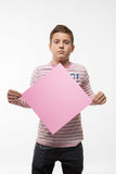 The artistic boy brunette in a pink jumper with a pink sheet of paper for notes Royalty Free Stock Images