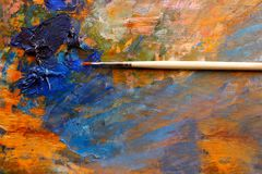 Artistic brush, background image of bright oil-paint palette closeup. On a wooden board royalty free stock photography