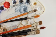 Artistic brush and color. Painting brushes and artistic color palette on white paper Stock Photography