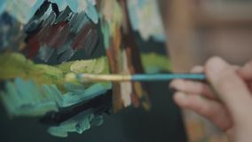 Detail view of brush of artist, touching canvas, drawing a picture. Artistic brush of painter is applying colours on canvas, close-up. Artist is using oil paints stock video