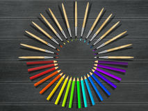 Artistic brushes and colored pencils on wooden table. Tools assortment. Royalty Free Stock Image