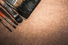 Artistic brushes on wooden background. Dirty black brushes of different sizes on the wooden backdrop Royalty Free Stock Image
